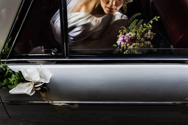 """Fotografía de bodas """"Coche de boda y novia con flores"""""""