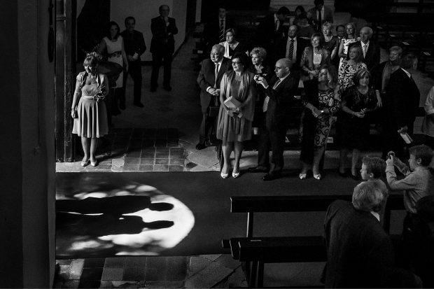 """Fotografía de bodas """"Entrada de novios son sombra en iglesia"""""""